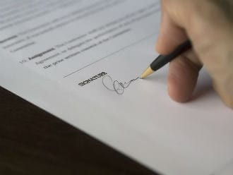 pen in hand signing a contract